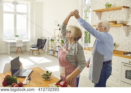 Positive Senior Couple Having Fun While Cooking A Healthy Meal At Home Together
