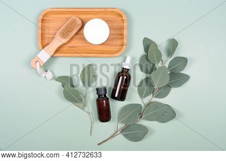 Essential Oils, Facial Creme Container And Massage Brush With Natural Eucalyptus Leaves On Green Bac