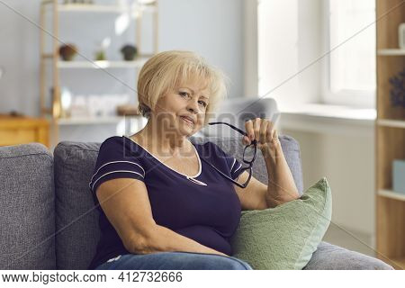 Wise Mature Woman Holding Glasses And Looking At Camera Sitting On Sofa At Home