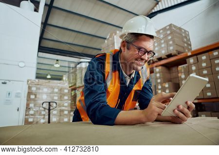 Smiling Factory Worker Leaning On Table At Warehouse Looking At Digital Tablet