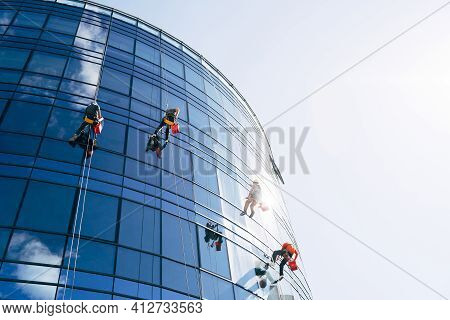 Industrial Climbers Cleaning Blue Windows Outside Building.
