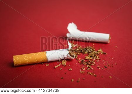 Broken Cigarette On Red Background, Closeup. Quitting Smoking Concept
