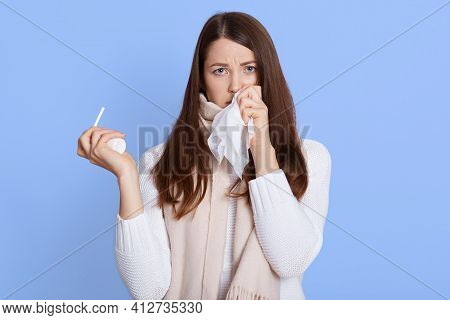 Dark Haired Unhealthy Caucasian Woman With Napkin Sneezing And Holding Throat Spray In Hands To Help