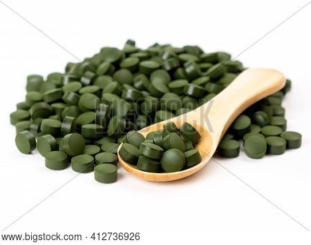 Spirulina Algae Tablets With A Wooden Spoon Isolated On White Background. Nutritional Supplements, V