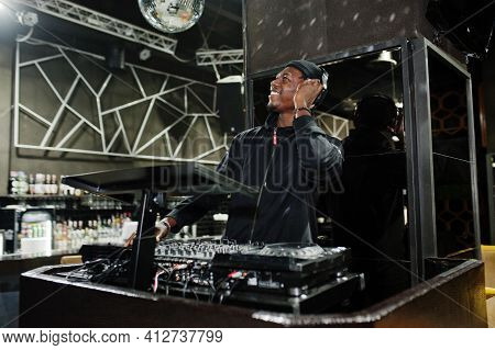 African American Dj Play Music On Decks At Night Club.