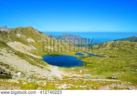 View from the Col de Bastanet on the Lac De La Hourquette lake in Neouvielle national nature reserve, department of Hautes-Pyrenees, Occitanie in south of France. Mountain landscape in sunny day.