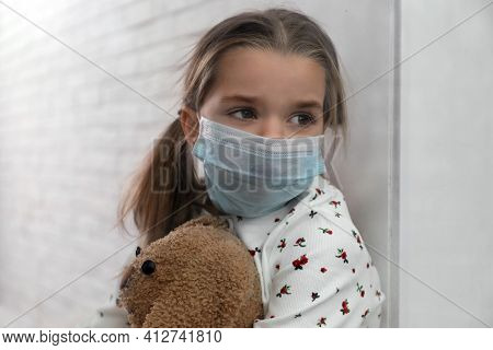 Sad Little Girl In Protective Mask Looking Out Of Window Indoors, View From Outside. Staying At Home