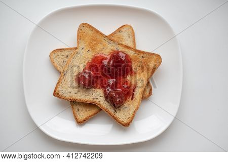 Two Golden Toasted Toast With Strawberry Jam For Breakfast On A White Plate