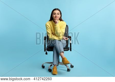 Young Woman Sitting In Comfortable Office Chair On Turquoise Background