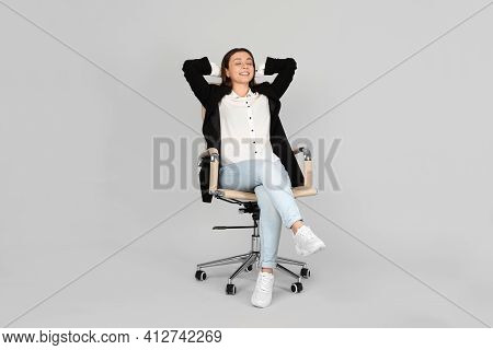 Young Woman Relaxing In Comfortable Office Chair On Grey Background