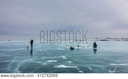Thick Transparent Ice With Islands Of Snow Is Streaked With Cracks. Two People Are Ice Fishing. Next