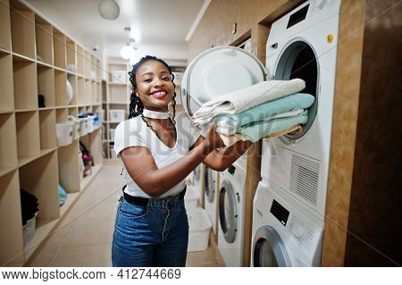 Cheerful African American Woman With Towels In Hands Near Washing Machine In The Self-service Laundr
