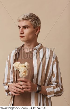 Vertical Portrait Of Feminine Blonde Man Holding Flowers While Standing Against Neutral Beige Backgr