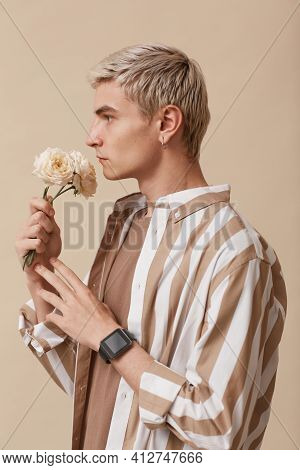 Vertical Side View Portrait Of Feminine Blonde Man Holding Flowers While Standing Against Neutral Be