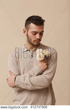 Vertical Waist Up Portrait Of Feminine Young Man Holding Flowers While Standing Against Neutral Beig