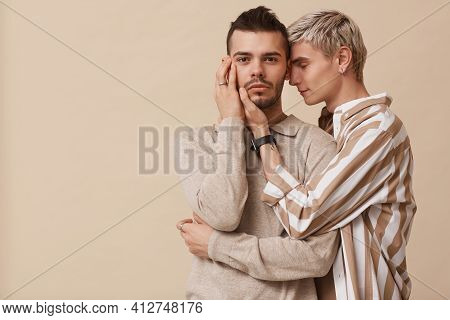 Minimal Waist Up Portrait Of Young Gay Couple Embracing Gently While Posing Against Beige Background