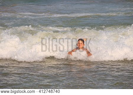 Child Swims In The Sea Waves On The Beach