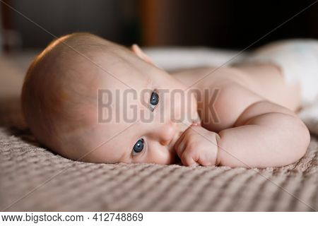 Fair-haired Child Is Lying On The Bed At Home With A Thoughtful Look Out The Window. Keeps A Finge I