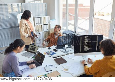 High Angle View At Multi-ethnic Software Development Team Using Computers And Writing Code While Col