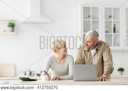 Smiling Senior Couple Spouses Use Laptop, Calculator, New Technology Paying Banking Bills Online