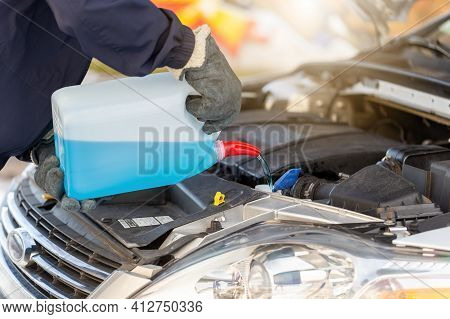 Person Pouring Antifreeze To The Car In Wintertime
