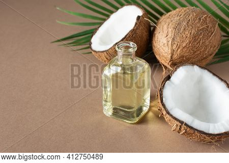 Bottle Of Coconut Oil And Fresh Coconuts With Palm Leaf On Brown Background. Coconut Natural Cosmeti