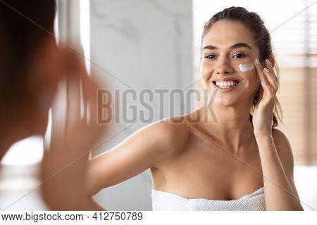Woman Applying Cream Under Eyes Moisturizing Skin Posing In Bathroom