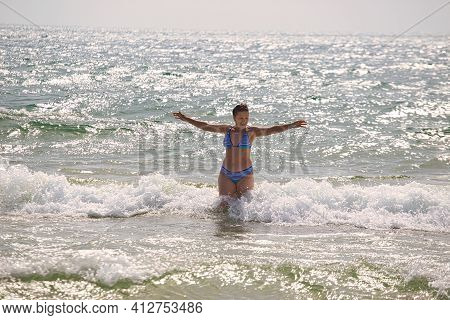 Woman Bathes In Sea Waves On The Beach