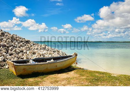 Old Rustic Bot Next To A Pile Of Mussels On The Sandy Beach Of The Caribbean Island In Bonaire. Neth