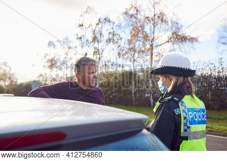 Male Driver Being Stopped By Female Traffic Police Officer For Driving Offence