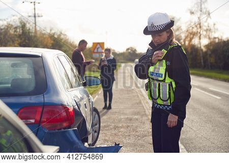 Female Traffic Police Officer Reporting Details Of Road Traffic Accident On Radio