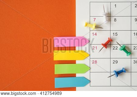 Thumbtacks And Paper Tag On White Calendar With Grunge Orange Paper Background For Planning, Meeting