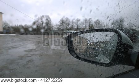 Blurred Abstract Image Of City Street Through The Automobile Glass With Raindrops. Rainy Sad Overcas