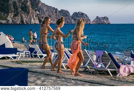Alanya , Turkey- October 20, 2020: Beautiful young girls dance on  Cleopatra's beach  on suny day Alanya. Turkey.