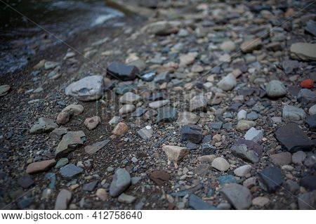 Pebbles And Colored Pebbles In Water Close-up. Texture Of Mixed Different Sizes Stones On The Shore