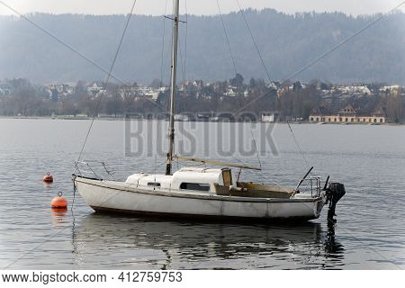 Old Interesting Boat With Black Outboard Motor Floats Leaderless On The Water, The Anchor Was Laid