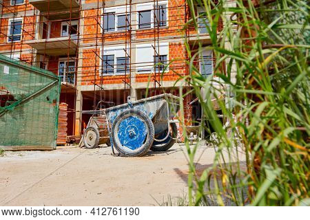 Used Industrial Obsolete Wheelbarrow Placed On Building Site, Scaffold Placed Against Edifice Under