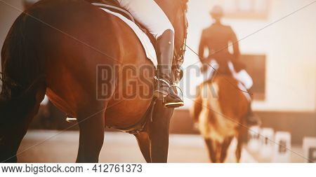 Two Beautiful Horses With Riders In The Saddle Participate In Dressage Competitions, Illuminated By