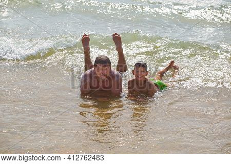 Family Swims In Sea Waves On The Beach 2021