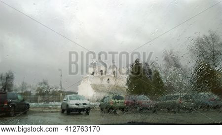 Blurred Abstract Image Of City Street, Car Parking And White Church Through Wet Window Glass With Ra