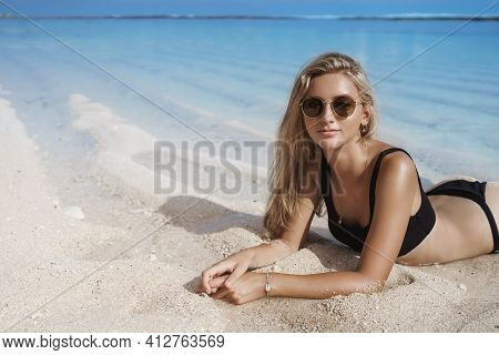 Blond Female Tourist In Bikini Sunbathing On Tropical Beach. Girl Lying On Shore In Sunglasses, Rela