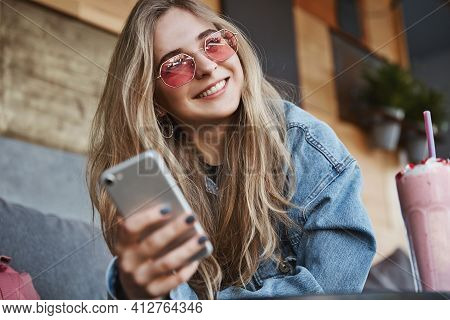 Stylish Young Woman In Sunglasses Sitting Outdoor Cafe And Using Mobile Phone, Smiling And Looking O