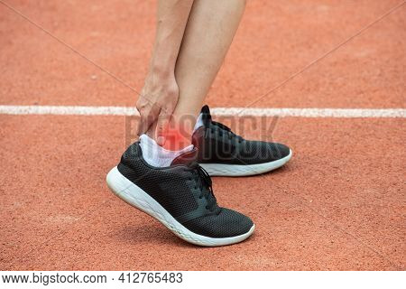 Close Up Of Runner Woman Holding Her Ankle, Suffering From Ankle Pain After Running. Conceptual Of I