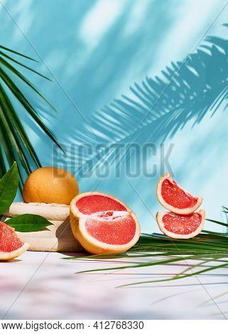 Fresh Healthy Grapefruit On Sunlight With Hard Shadows. Minimal Food Creative Concept On Blue Pastel