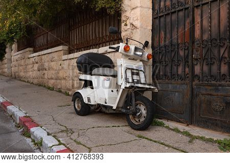 Jerusalem, Israel, February 27, 2021 : Evening View Of An Old Small Scooter Standing On Benjamin Dis