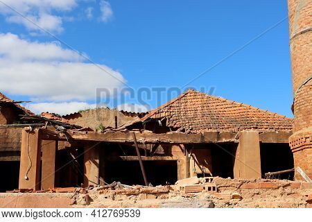 Brick Building After Fire With Destroyed Tiled Roof Against Blue Sky. Broken And Destroyed Roof Of A
