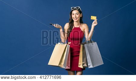 Happy Young Asian Woman Showing Credit Card And Using Mobile Phone For Online Shopping On Blue Color