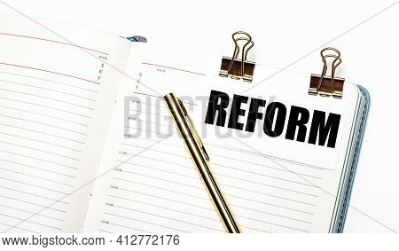 On A Light Background, An Open Notebook, A Sheet Of Paper With Gold Clips And The Text Reform And A