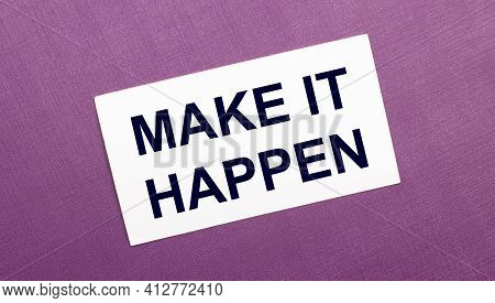 On A Lilac Background, A White Card With The Words Make It Happen