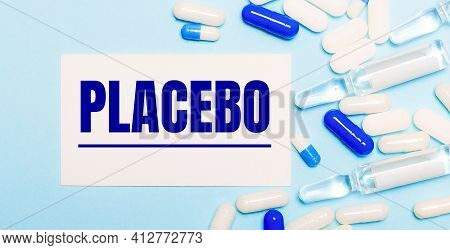 Pills, Ampoules And A White Card With The Text Placebo On A Light Blue Background. Medical Concept
